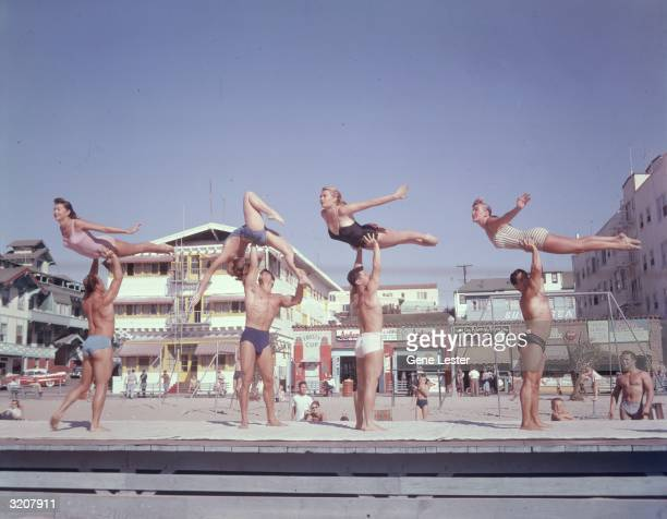 Fulllength image of stunt performers on Muscle Beach Santa Monica California Four men lift four women in the air all in bathing suits on the...