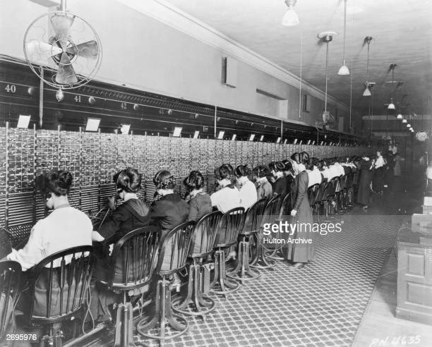 Fulllength image of telephone operators sitting in front of a long switchboard at the Cortlandt Exchange in New York City