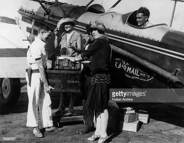 Fulllength image of two women removing pearls from a trunk carried by two postal workers next to a US airmail plane