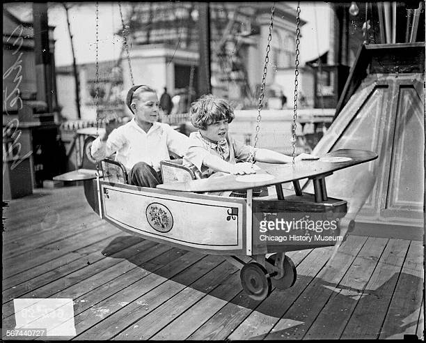 Fulllength portrait of a girl and boy sitting in a small airplane on a ride at the White City amusement park located at 63rd and South Parkway in the...