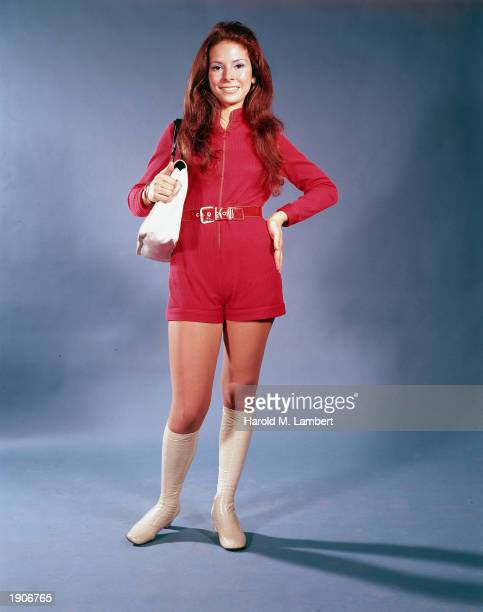 Fulllength portrait of a model wearing red mini jumpsuit with white gogo boots and matching shoulder bag late 1960s