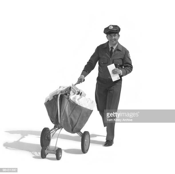 Fulllength portrait of a smiling mailman as he pushes a mail carrier with one hand and holds several letter in the other 1967