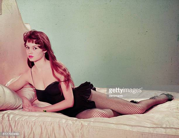 Full-length portrait of actress and sex symbol Brigitte Bardot, reclining on bed wearing a black teddy with fishnet stockings.