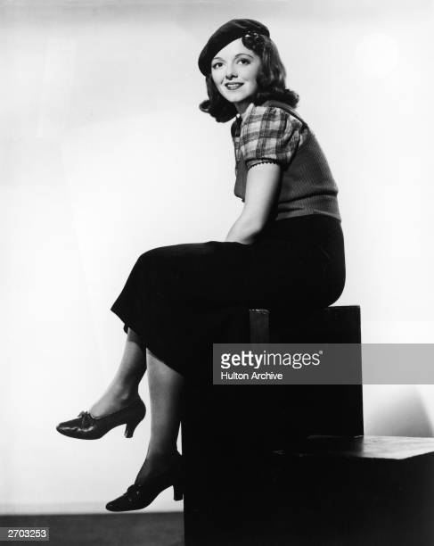 Fulllength portrait of American actor Janet Gaynor wearing a beret and sweater vest and sitting on a cube circa 1940