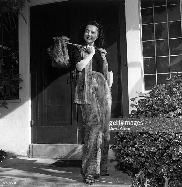 Fulllength portrait of American actor Lynn Bari modeling a fur vest fur pants and a fur satchel while standing on a front porch Hollywood California...