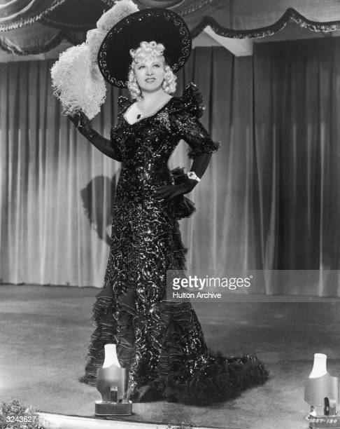 Full-length portrait of American actor Mae West standing on stage wearing a long ruffled and sequined dress and a plumed hat, from director Edward...