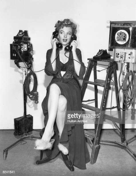 Fulllength portrait of American actor Marilyn Monroe holding a telephone receiver to either ear while sitting on a stool in lingerie and...