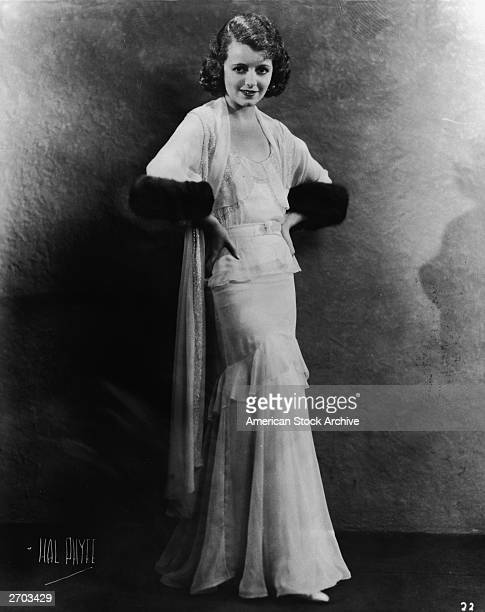 A fulllength portrait of American actress Janet Gaynor posed with her hands on her hips and wearing a gown and matching jacket with fur trimmed...