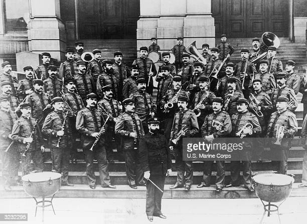 Fulllength portrait of American composer and marching band leader John Philip Sousa and his band wearing their uniforms and holding their instruments...