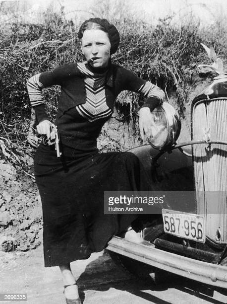 Full-length portrait of American criminal Bonnie Parker smoking a cigar while leaning on the front fender of a car and holding a pistol.