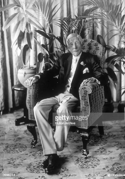 Fulllength portrait of American industrialist and philanthropist John D Rockefeller seated in a chair at Golf House Lakewood New Jersey Some large...