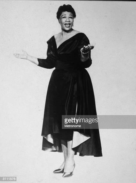 Fulllength portrait of American jazz singer Ella Fitzgerald singing and wearing a dark evening dress 1950s