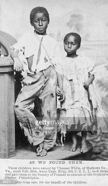 Fulllength portrait of an AfricanAmerican brother and sister former slaves holding hands while wearing ripped and torn clothing They were owned by...