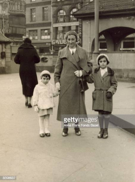 A fulllength portrait of Anne Frank her mother Edith FrankHollander and her sister Margot Frank holding hands at the Hauptwache in the center of...