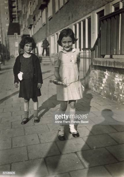 A fulllength portrait of Anne Frank holding a jumping rope and her friend Sanne Ledermann standing on a sidewalk in Merwedeplein Amsterdam the...