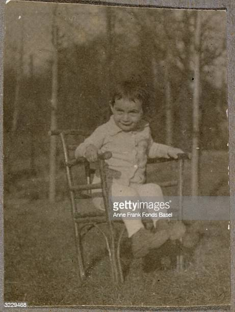 A fulllength portrait of Anne Frank sitting on a lawn in a small chair Frankfurt am Main Germany From Anne Frank's photo album