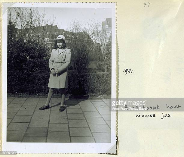 Fulllength portrait of Anne Frank wearing a hat and coat standing on a sidewalk in front of shrubbery taken from her photo album Amsterdam Holland