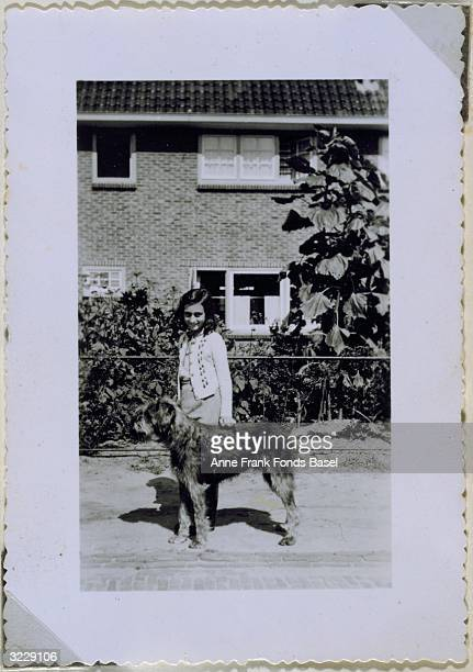 Fulllength portrait of Anne Frank with Dopy the dog taken from her photo album Laren