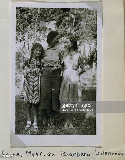 Fulllength portrait of Anne Frank's friend Sanne Ledermann with her mother and sister Barbara Ledermann in dappled sunlight taken from Anne Frank's...