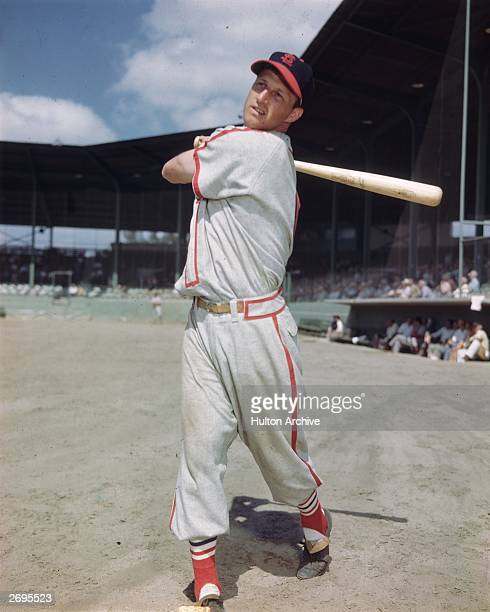 Fulllength portrait of baseball player Stan Musial of the St Louis Cardinals swinging a baseball bat in front of a stadium audience