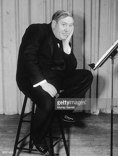 Fulllength portrait of British actor and director Charles Laughton sitting on a tall stool with his chin resting in his hand Los Angeles California...