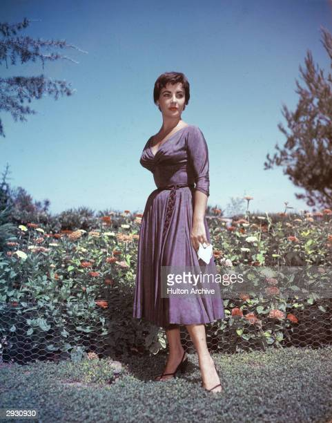 Full-length portrait of British-born actor Elizabeth Taylor as she stands in a garden and holds a handkerchief in her right hand, circa 1950s.