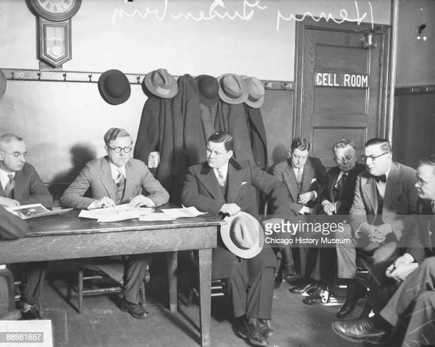 Fulllength portrait of Henry Gusenberg and Dr Herman N Bundesen Cook County Coroner sitting at a table in a room in Chicago Illinois during an...