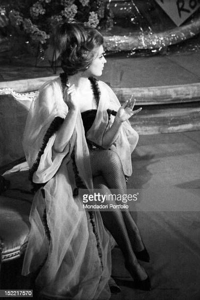 Fulllength portrait of Ilaria Occhini in the role of Anna She is sat down with crossed legs with a sigarette in her hand Teatro Lirico Milan November...