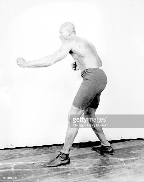 Fulllength portrait of Jack Johnson African American heavyweight champion boxer throwing a right jab with his left side to the camera standing in...