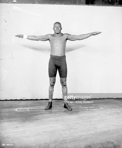 Fulllength portrait of Jack Johnson African American pugilist extending his arms at his sides standing in front of a lightcolored backdrop in a room...