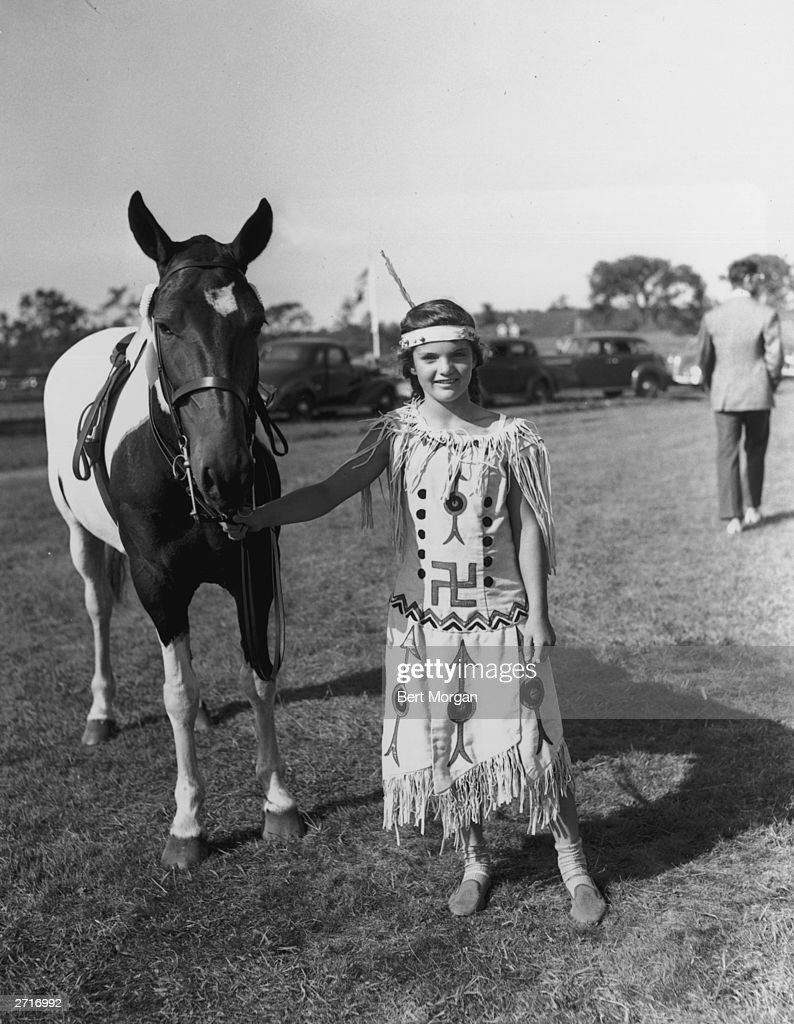 Full-length portrait of Jacqueline Bouvier (1929 - 1994), daughter of Mr and Mrs John V Bouvier III, dressed in an American Indian costume and standing with her piebald pony, 'Dance Step,' at the East Hampton Horse Show, East Hampton, Long Island, New York.