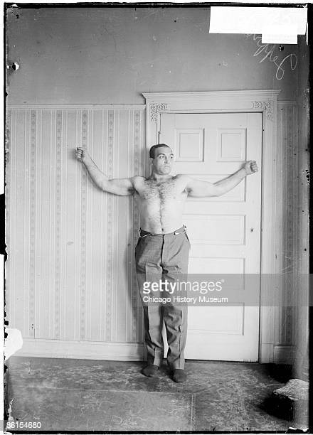 Fulllength portrait of James J Jeffries pugilist standing with arms spread to sides against a wall in a room in Chicago Illinois 1905 His mouth is...