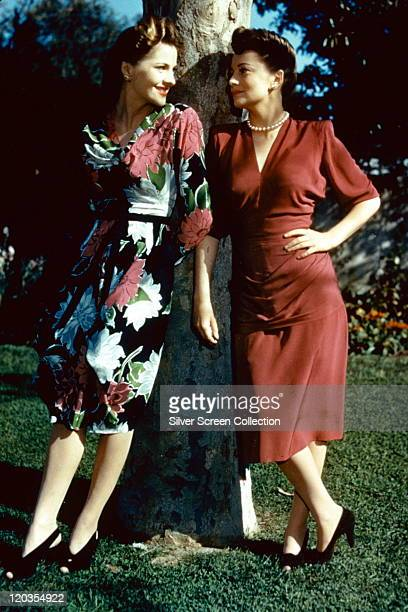Fulllength portrait of Joan Fontaine and her sister Olivia de Havilland both British actress standing in conversation by a tree circa 1945