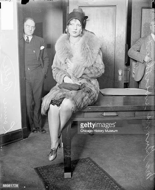 Fulllength portrait of Louise Rolfe girlfriend and sweetheart of Jack McGurn looking to her right and sitting on a table in a room in Chicago...