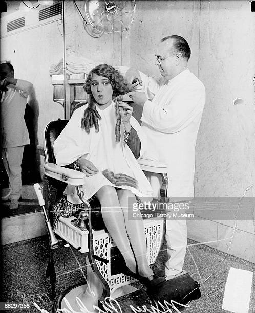 Fulllength portrait of movie actress Mary Pickford sitting in a chair in a barber shop in Chicago Illinois having her long curls cut off by a barber...