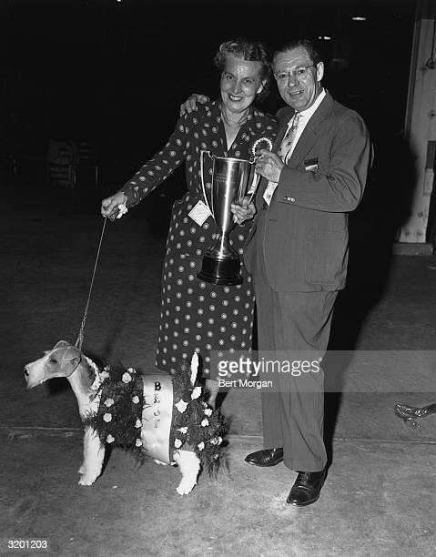 Fulllength portrait of Mrs Arbutus Forslund and Lorris Warden a judge holding the trophy that Forslund's whitehaired terrier won for 'Best in Show'...