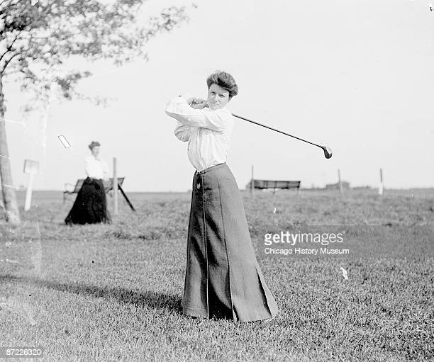 Full-length portrait of Mrs. T. A. Alexander, golfer, swinging a club over her shoulder, standing on golf course at Chicago Golf Club in Wheaton,...
