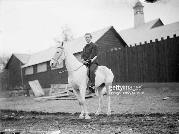 Fulllength portrait of polo player sitting in saddle on a white horse in a paddock area near a barn at an equestrian facility in or near Chicago...