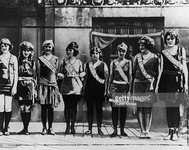 Full-length portrait of the first Miss America contestants, wearing their sashes over swimsuits, standing in a line on the boardwalk in Atlantic...