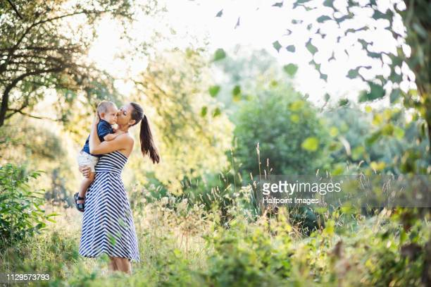 A full-length portrait of young mother holding a toddler son outdoors in nature in summer. Copy space.