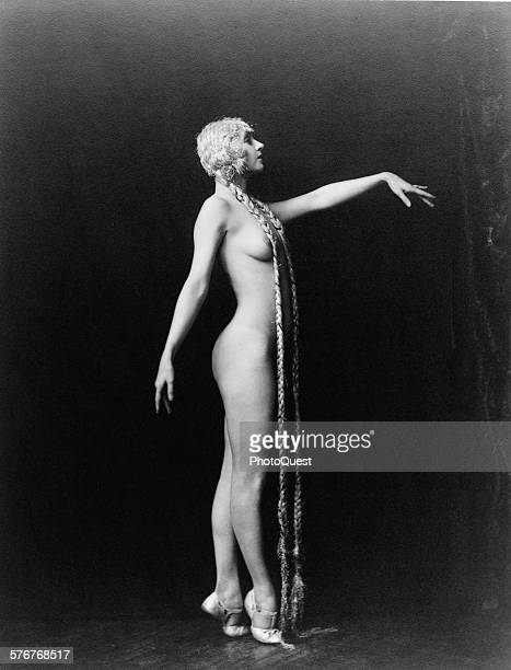 Fulllength portrait of Ziegfeld girl Evelyn Groues with long braids as she poses nude facing right and with her left arm raised circa 1925
