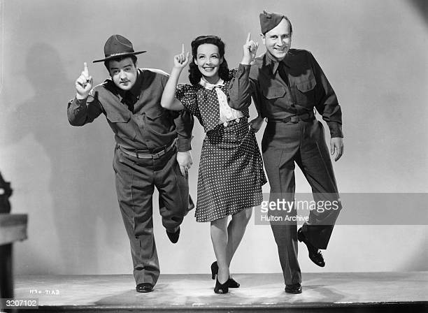 Fulllength promotional portrait of American comedy duo Bud Abbott and Lou Costello dancing with American actor Jane Frazee on the set of director...