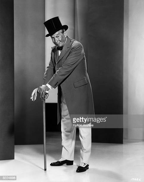 Fulllength promotional portrait of French actor and singer Maurice Chevalier wearing a top hat and standing with his hands folded atop his cane for...