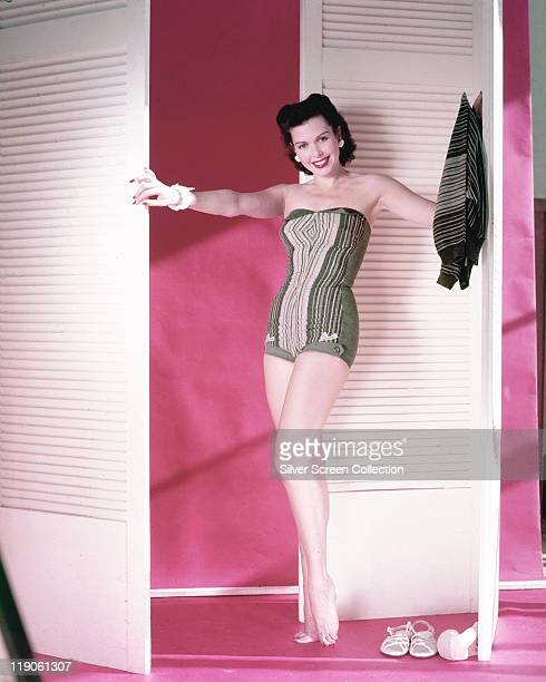 Fulllength shot of Ann Miller US actress poses wearing a swimsuit between two white louvre doors circa 1950