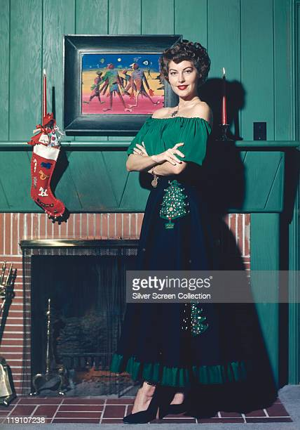 Full-length shot of Ava Gardner , US actress, wearing a dress decorated with Christmas trees, standing by a fireplace, above which hangs a Christmas...