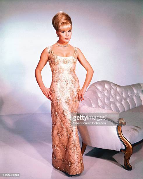 Full-length shot of Elke Sommer, German actress, wearing a long sleeveless dress with her hair in a beehive hairstyle, standing beside a sofa, in a...