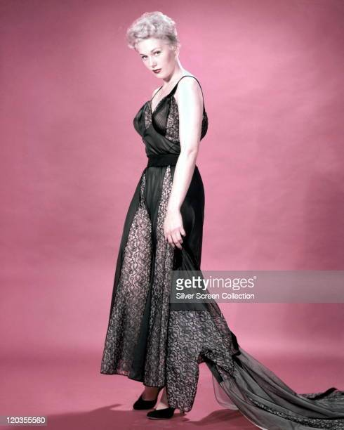 Fulllength shot of Kim Novak US actress wearing a long black silk and black lace dress with a black lace train in a studio portrait against a red...