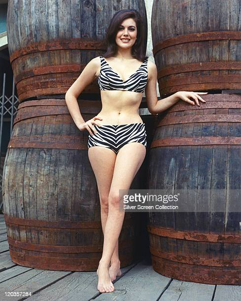 Fulllength shot of Linda Harrison US actress and model wearing a blackandwhite tiger print bikini posing in front of a stack of wooden barrels circa...