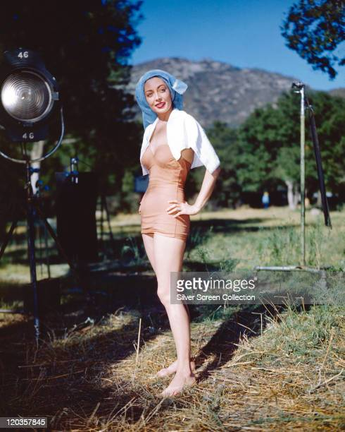 Fulllength shot of Marie Windsor US actress wearing a salmon pink bathing costume with a white towel draped over her shoulders and blue towel on her...