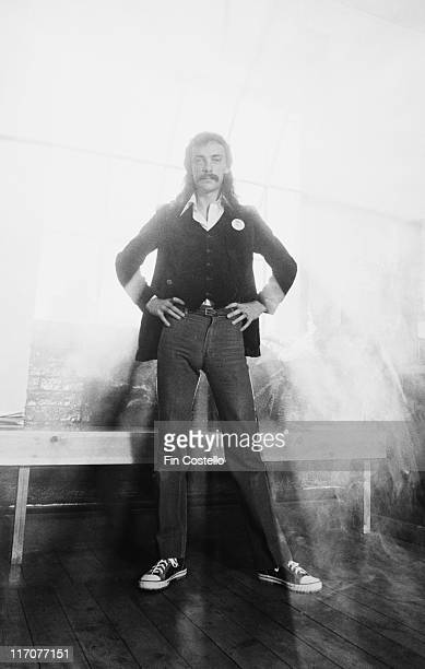 Fulllength shot of Neil Peart drummer with Canadian rock band Rush poses with his hands on his hips with a bright white light behind him in a studio...